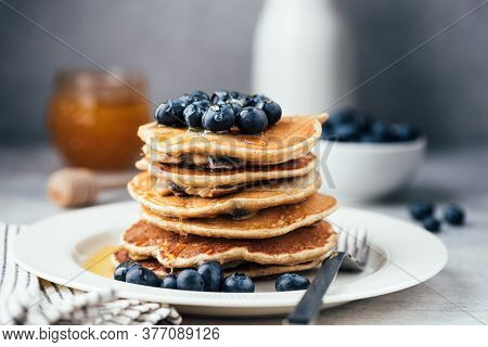 Oat Pancakes With Blueberries And Honey On White Plate. Stack Of Healthy Vegetarian Pancakes, Low Ca