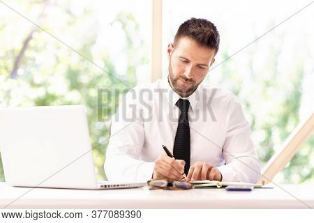 Shot Of Confident Businessman Writing Something While Sitting At Office Desk Behind His Laptop And W