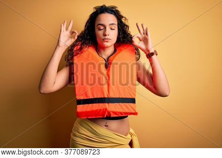 Young beautiful woman with curly hair wearing orange lifejacket over yellow background relax and smiling with eyes closed doing meditation gesture with fingers. Yoga concept.