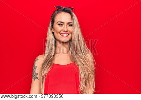 Young beautiful blonde woman wearing red t-shirt and sunglasses over isolated background with a happy and cool smile on face. Lucky person.