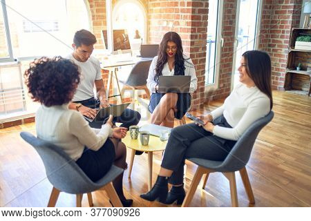 Group of business workers smiling happy and confident. Sitting on chairs relaxed with smile on face. Speaking taking rest at the office