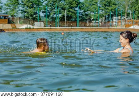 Little Toddler Boy With Inflatable Armbands Aids Playing In Water With Mother In Lake Water