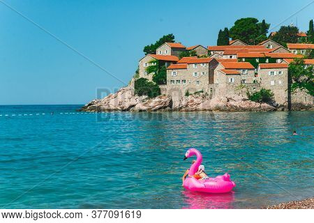 Sveti Stefan, Montenegro - July 18, 2018: Family Swimming In Sea With Pink Inflatable Flamingo