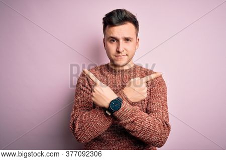 Young handsome caucasian man wearing casual winter sweater over pink isolated background Pointing to both sides with fingers, different direction disagree