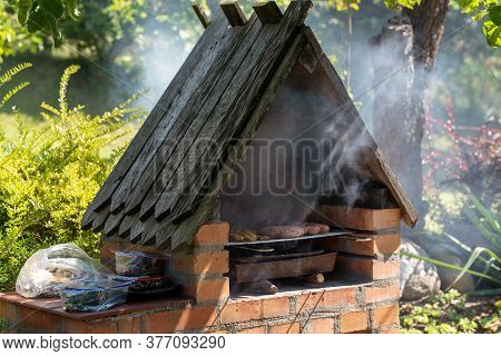 Grilling Sausages And Meat On Barbecue Grill. Barbeque Grill Fireplace.