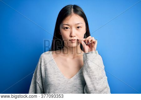 Young beautiful asian woman wearing casual sweater standing over blue isolated background mouth and lips shut as zip with fingers. Secret and silent, taboo talking