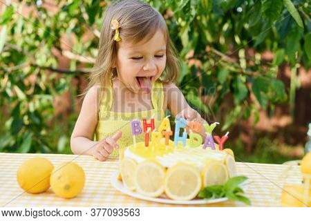 Birthday Cake With Happy Birthday Candles. Little Child Drinks Natural Lemonade At Stand In Park