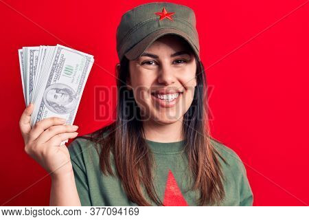 Woman wearing t-shirt with red star communist symbol holding bunch of dollars banknotes looking positive and happy standing and smiling with a confident smile showing teeth