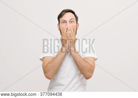 Close Portrait. Frightened Young Man Covers His Mouth With His Palms