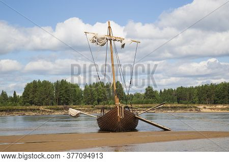 An Old Wooden Boat Stands On The Beach On A Sandy Beach.