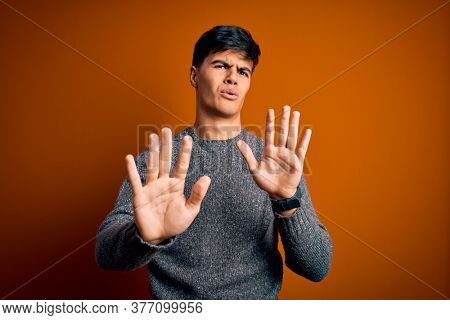 Young handsome man wearing casual sweater standing over isolated orange background Moving away hands palms showing refusal and denial with afraid and disgusting expression. Stop and forbidden.