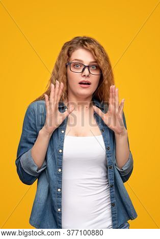 Astonished Young Female In Casual Outfit And Eyeglasses Looking At Camera And Gesticulating With Han