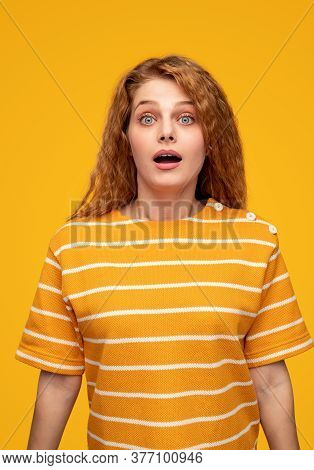 Amazed Young Redhead Female In Bright Striped Yellow Shirt Looking At Camera With Astonished Face Ag