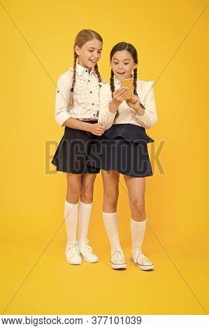 Girls School Uniform Using Smartphone. Schoolgirls Use Mobile Phone Or Smartphone To Share Photos. S