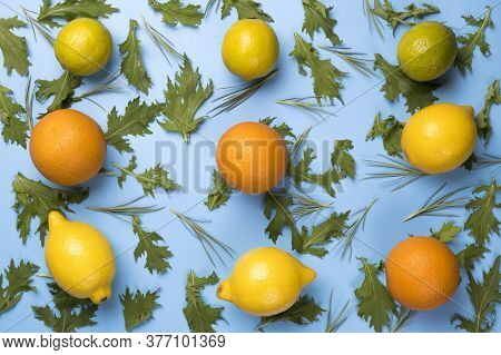 Close Up Of Citrus Fruits Orange, Lime And Lemon On Green Rucola Salad Leaves Pattern On Blue Backro