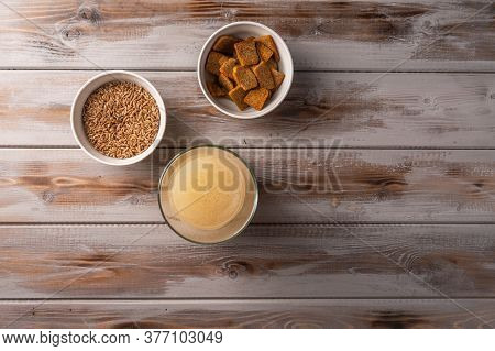 Top View Homemade Tradishional Russian Light Rye Kvass In Glass And Crackers On Wooden Background. W