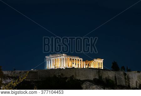 Acropolis Hill With Shiny Famous Parthenon Temple On Night Sky Background, Athens, Greece. This Plac