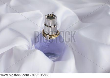 A Bottle Of Eau De Toilette On A White Draped Background. Perfume Ads.