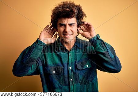 Young handsome man wearing casual shirt standing over isolated yellow background Trying to hear both hands on ear gesture, curious for gossip. Hearing problem, deaf