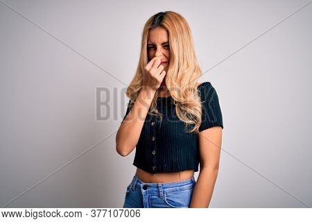 Young beautiful blonde woman wearing casual t-shirt standing over isolated white background smelling something stinky and disgusting, intolerable smell, holding breath with fingers on nose. Bad smell