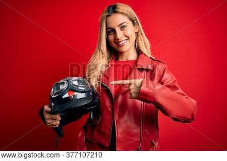 Young beautiful blonde motorcyclist woman holding moto helmet over isolated red background very happy pointing with hand and finger