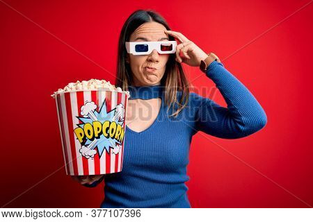 Young blonde woman wearing 3d glasses and eating pack of popcorn watching a movie on cinema worried and stressed about a problem with hand on forehead, nervous and anxious for crisis