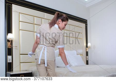 Maid Service In The Hotel Room. Cleaning Of Hotel Rooms. Girl In Uniform Adjusts Her Blanket On The