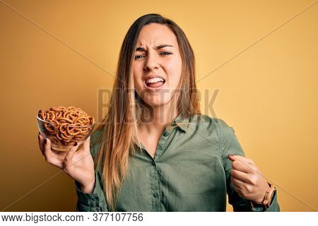 Young beautiful blonde woman with blue eyes holding bowl with german baked pretzels annoyed and frustrated shouting with anger, crazy and yelling with raised hand, anger concept