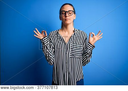 Beautiful blonde woman with blue eyes wearing striped shirt and glasses over blue background relax and smiling with eyes closed doing meditation gesture with fingers. Yoga concept.