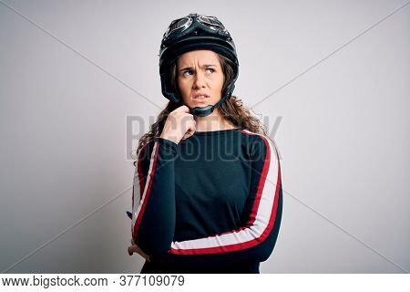 Beautiful motorcyclist woman with curly hair wearing moto helmet over white background with hand on chin thinking about question, pensive expression. Smiling with thoughtful face. Doubt concept.