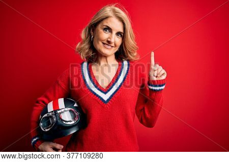 Middle age beautiful blonde motorcyclist woman holding moto helmet over red background surprised with an idea or question pointing finger with happy face, number one