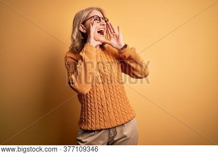 Middle age beautiful blonde woman wearing casual sweater and glasses over yellow background Shouting angry out loud with hands over mouth