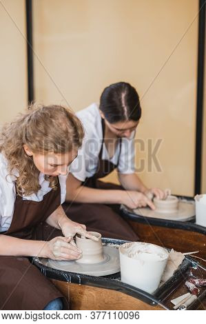 Two Girls Working On Potters Wheel Making Clay Handmade Craft In Pottery Workshop, Friendship And Gu