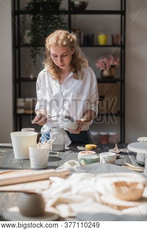 Female Potter Sitting And Stirs Paint With A Brush A Cup On The Table. Woman Making Ceramic Item. Po
