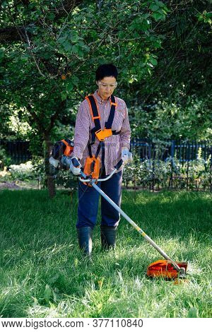 Adult Woman Mows The Grass In The Backyard Using String Trimmer. Garden Work Concept.
