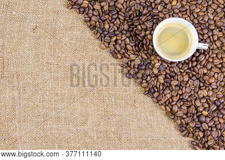 Coffee Beans On Burlap And A Cup Of Coffee. Coffee Beans On Burlap And A Cup Of Coffee. View From Ab