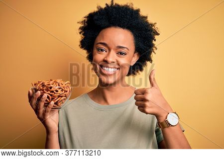 Young African American afro woman with curly hair holding bowl with baked German pretzels happy with big smile doing ok sign, thumb up with fingers, excellent sign