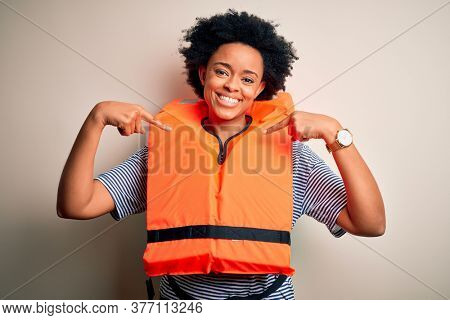 Young African American afro woman with curly hair wearing orange protection lifejacket looking confident with smile on face, pointing oneself with fingers proud and happy.