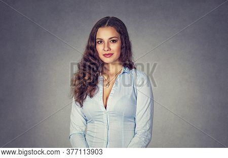 Portrait Of A Serious Young Woman Isolated On Studio Gray Background. Model Girl With Long Wavy Curl
