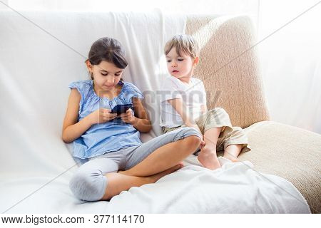 Children At Home Sitting On Sofa, Playing With Tablet. Cute Siblings Brother And Sister Have A Good