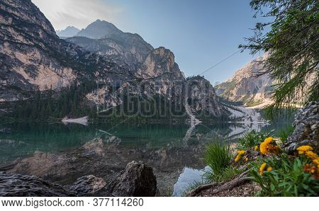 Braies Lake And Its Reflections Seen From A Beach Between Rocks And Tree Roots, Italian Landscape In
