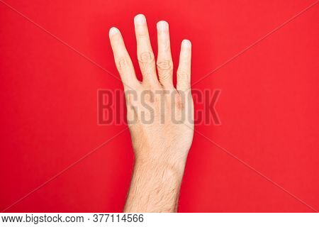 Hand of caucasian young man showing fingers over isolated red background counting number 4 showing four fingers