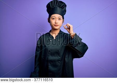 Young beautiful chinese chef woman wearing cooker uniform and hat over purple background mouth and lips shut as zip with fingers. Secret and silent, taboo talking