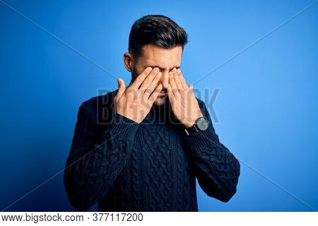 Young handsome man wearing casual sweater standing over isolated blue background rubbing eyes for fatigue and headache, sleepy and tired expression. Vision problem