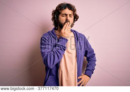 Young handsome sporty man with beard wearing casual sweatshirt over pink background bored yawning tired covering mouth with hand. Restless and sleepiness.