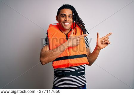 Young african american afro man with dreadlocks wearing orange lifejacket smiling and looking at the camera pointing with two hands and fingers to the side.