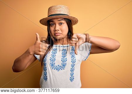Young beautiful asian girl wearing casual t-shirt and hat standing over yellow background Doing thumbs up and down, disagreement and agreement expression. Crazy conflict