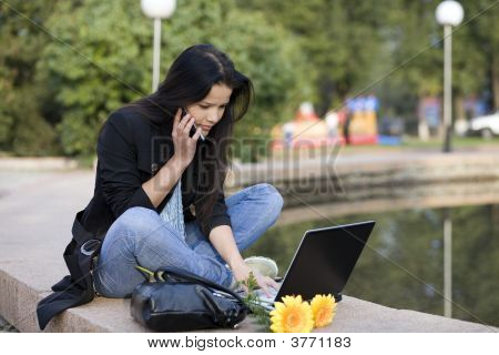 Girl With Laptop In Park