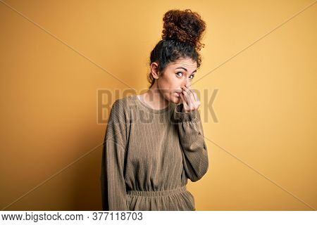 Young beautiful brunette woman with curly hair and piercing wearing casual dress smelling something stinky and disgusting, intolerable smell, holding breath with fingers on nose. Bad smell