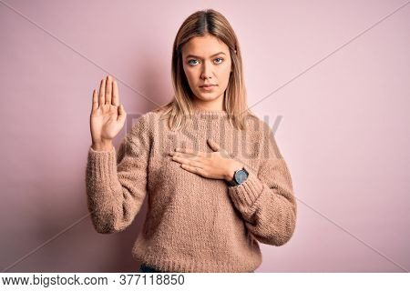 Young beautiful blonde woman wearing winter wool sweater over pink isolated background Swearing with hand on chest and open palm, making a loyalty promise oath